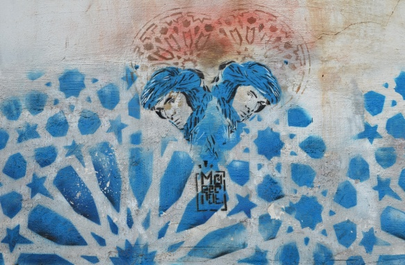 a blue stencil that looks like a Moroccan tile pattern, with an inset of a heart shape with top part red and bottom part two men's heads back to back, both with blue head scarves