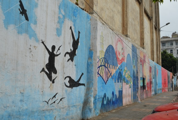 part of a series of murals on a Casablanca wall, three black silhouette figures jumping