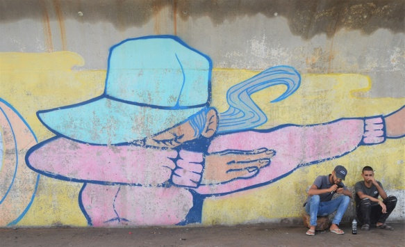 two men sitting in front of a mural with woman in pink shirt and turquoise hat, holding arm in front of her face