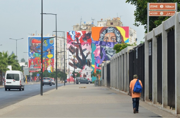 a man walks along a wide sidewalk, walking towards buildings with large colourful murals