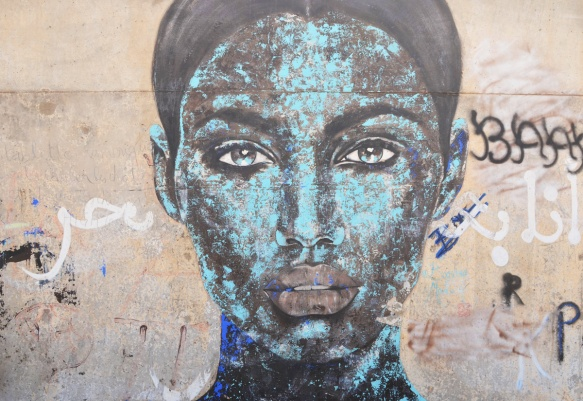 mural on a wall in Casablanca, blue woman's face with black cloth around top of head