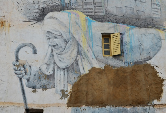 on a wall with a small window with open yellow shutter, a mural of an older woman with head scarf, bent over, and walking with a stick