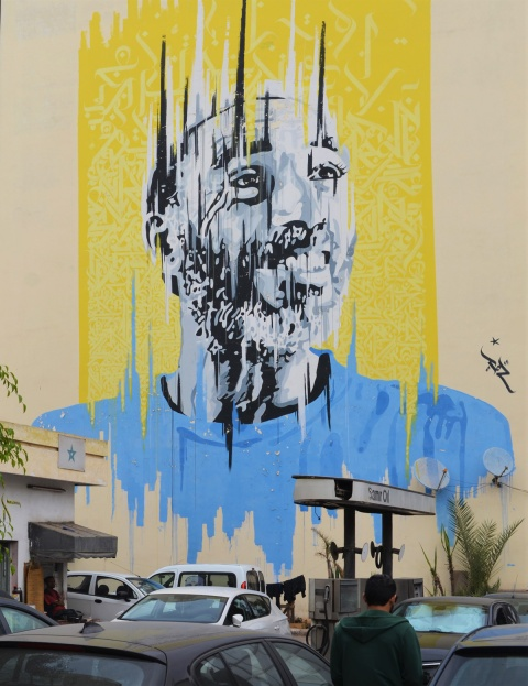 large mural painted by Yann Chatelin of a man in a blue T shirt, with yellow background, Casablanca gas station in the foreground