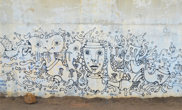black line drawing mural on a wall, with faces