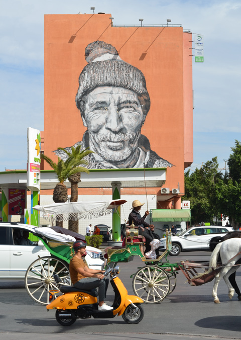 traffic passing by including a horse drawn carriage, a gas station on the corner across the street and a large mural of a berber man on a wall. Mural by Heinrich