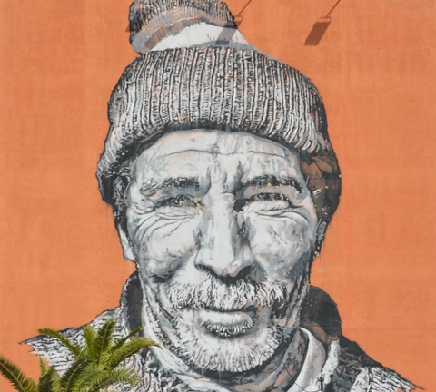 face of berber man in mural in Marrakech, part smile, wearing hat, mustache, wrinkled face
