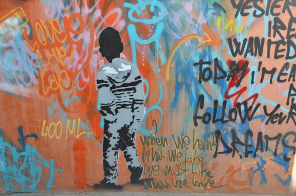 middle section of a mural by 400 ml in Marrakech, a boy in black and grey, back turned, against wall of bright reds and blues with words, love, love, love as well as