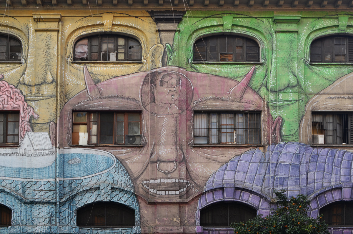 mural in Rome by Blu, on del porto fluviale, of large faces, where the eyes are windows in the buildings, brown face in middle