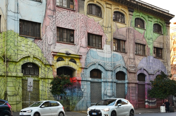 mural in Rome by Blu, on del porto fluviale, of large faces, where the eyes are windows in the buildings,