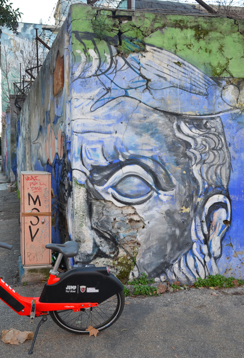corner of wall, painted face, mural on both sides of the corner, rental bike, jump, parked in front