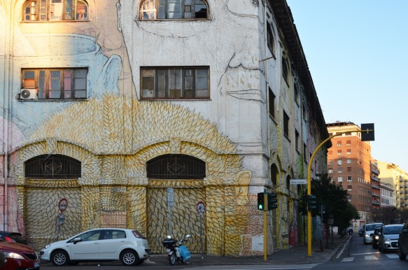 mural in Rome by Blu, on del porto fluviale, of large faces, where the eyes are windows in the buildings, at corner with via della conce