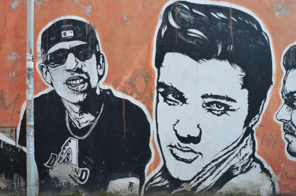 Elvis Presley and a rapper, large portraits by sten and lex, Italian street arts, in a mural on two sides of the street, of famous people and common people,