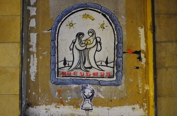 street art paste up of a nativity scene, Mary and Joseph standing together with Mary holding the baby Jesus, under night sky with moon and stars. The word refugees is written below the picture. All contained in a grey arch shape