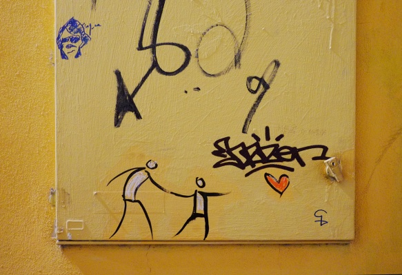 two stick figure people holding hands and reaching for a red heart