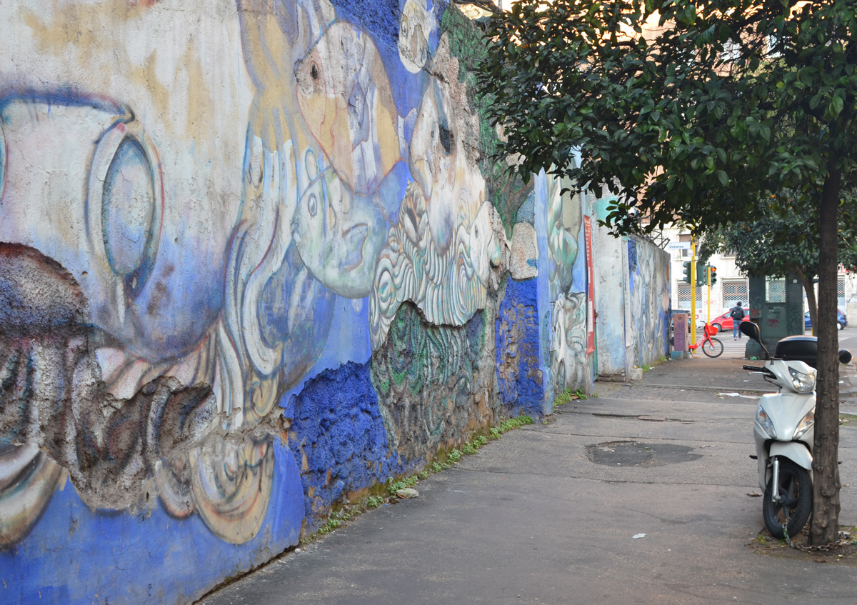 wall with old mural, pieces of wall, breaking off, tree beside woth motorcyle