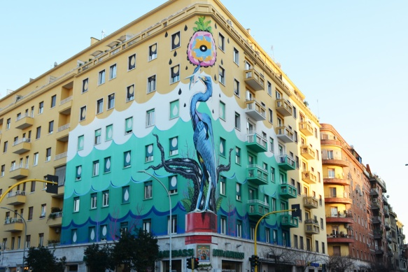 Lower part of a large mural called Hunting Pollution by Federico Massa also known as Iena Cruz, of a heron, over seven storeys of a building in Rome, background in marine blues and greens