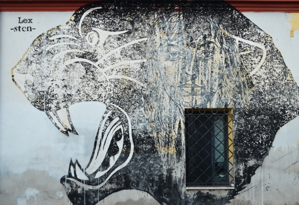 a large panther head in profile, with mouth wide open and teeth showing, a woman superimposed onto the side of the face of the panther, mural by sten and lex called black and white power