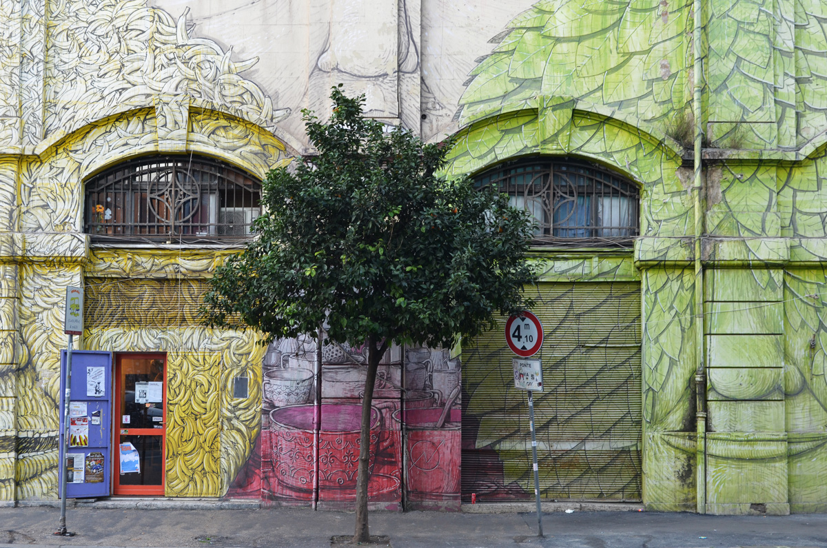 mural in Rome by Blu, on del porto fluviale, of large faces, where the eyes are windows in the buildings, small tree growing in front, green face and yellow face made of bananas