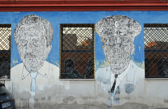 large portraits by sten and lex, Italian street arts, in a mural on two sides of the street, of famous people and common people,
