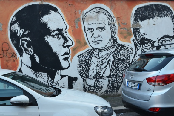 pope and others, large portraits by sten and lex, Italian street arts, in a mural on two sides of the street, of famous people and common people,