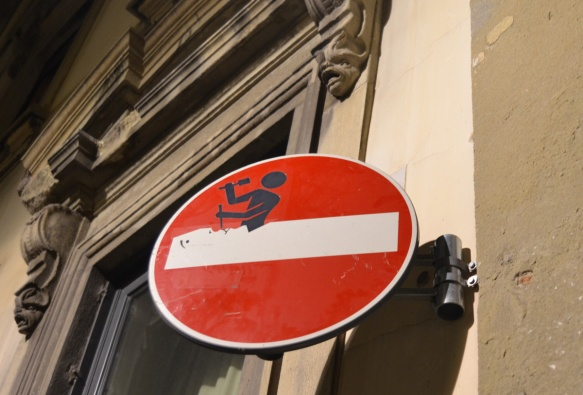 altered red and white no entry sign, graffiti by Clet Abraham, of a man chiseling away the white bar
