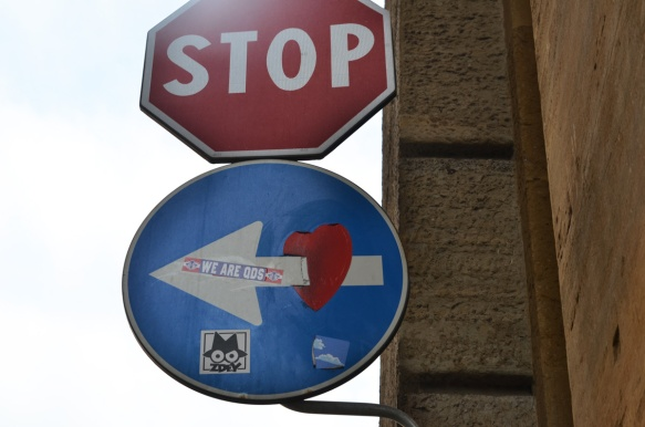 altered blue and white one way sign, the arrow is now piercing a red heart