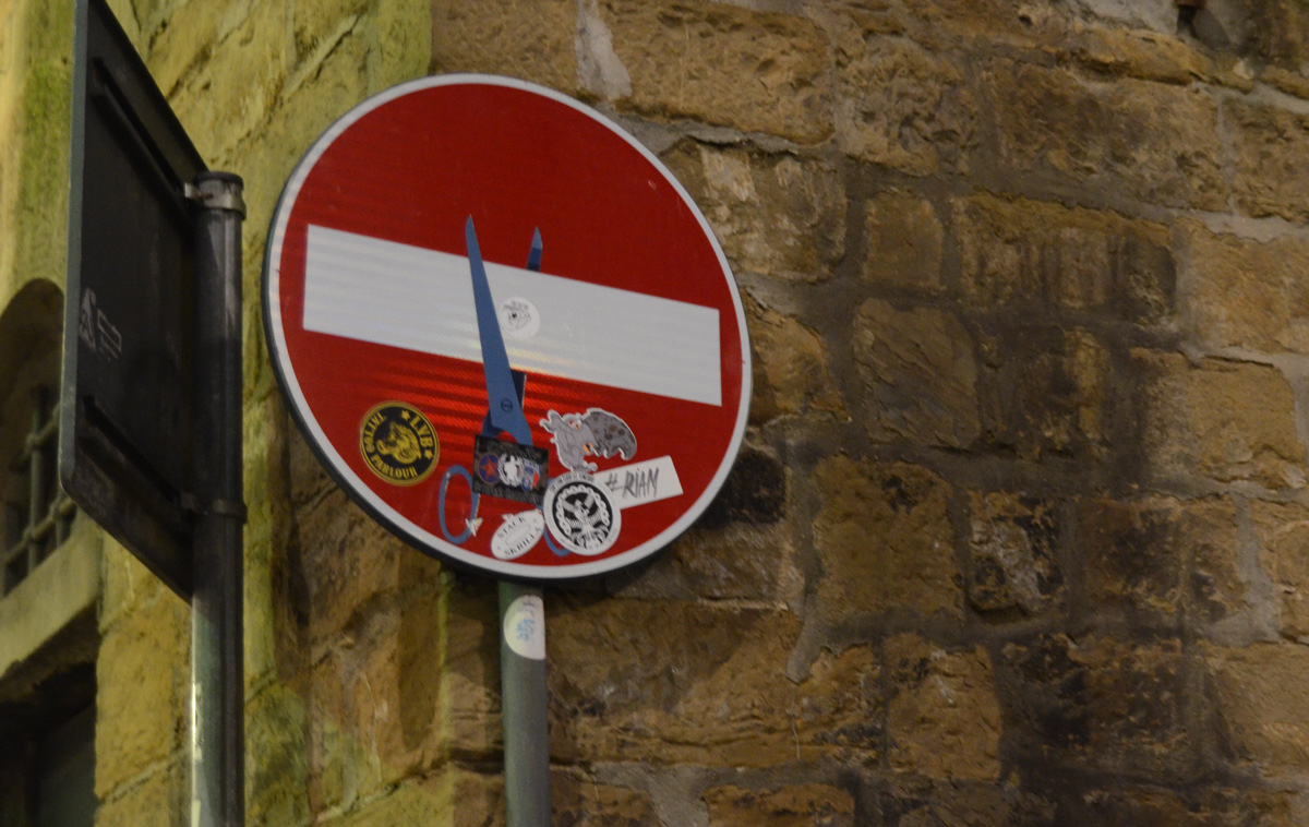 altered red and white no entry sign, graffiti by Clet Abraham, of a pair of scissors cuttig the white bar