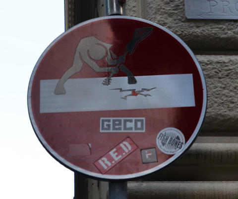 altered red and white no entry sign, graffiti by Clet Abraham, of a person breaking ice with a large ice pick