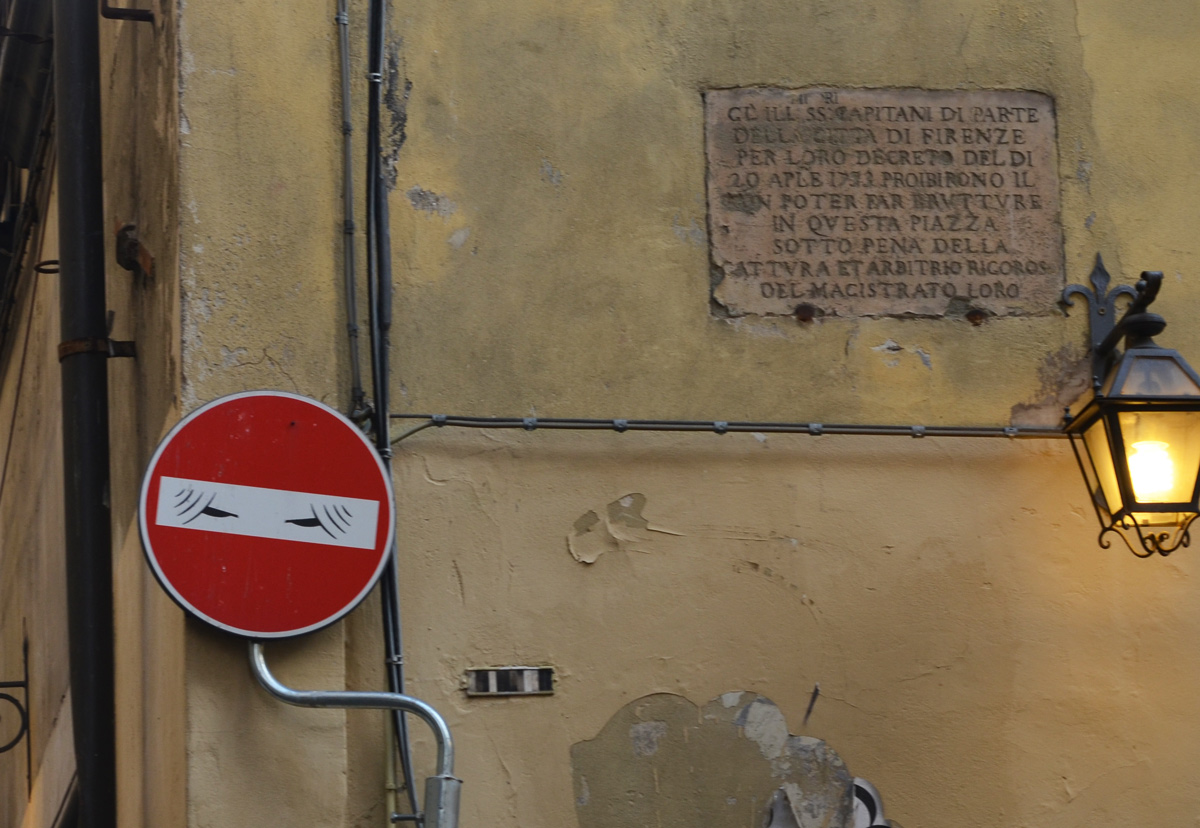 altered red and white no entry sign, graffiti by Clet Abraham, of a woman in a veil covering all but her eyes