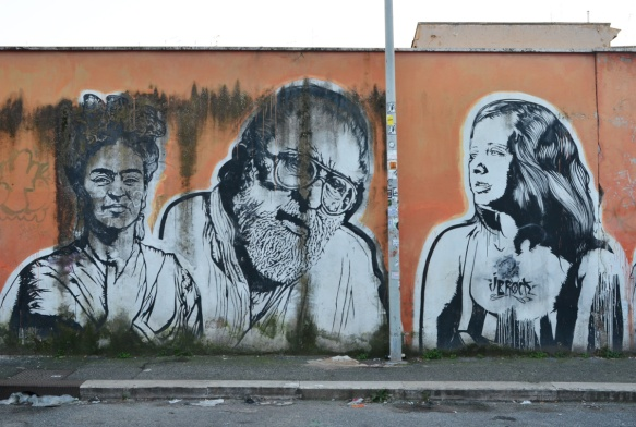 three people, large portraits by sten and lex, Italian street arts, in a mural on two sides of the street, of famous people and common people,