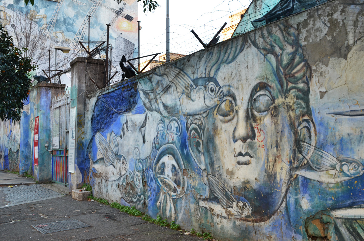 faces and fish on blue background, painted mural on wall with barbed wire above it, another mural on the wall beyond as well