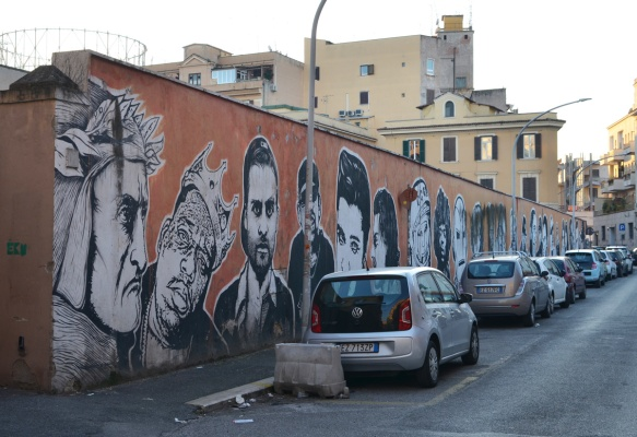 long orange wall with large portraits by sten and lex, Italian street arts, in a mural on two sides of the street, of famous people and common people,