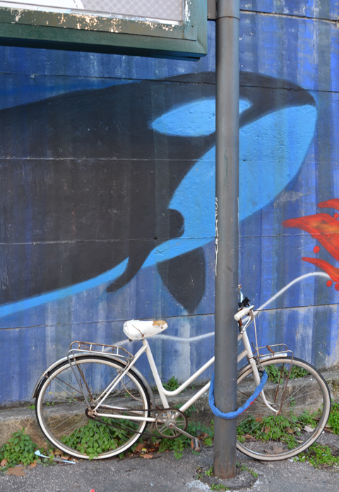 bike parked against a post in front of mural with a whale