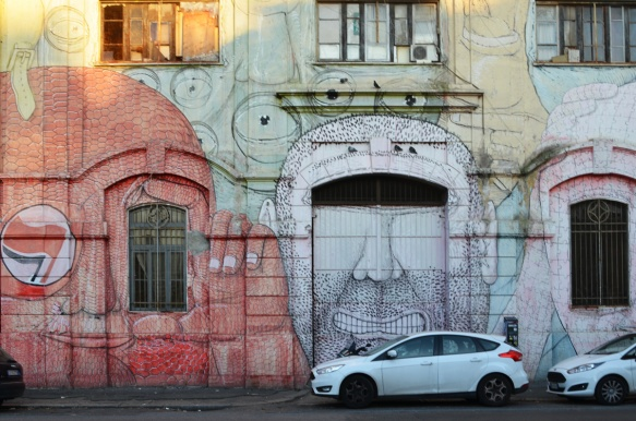 mural in Rome by Blu, on del porto fluviale, of large faces, where the eyes are windows in the buildings, red face and white face,