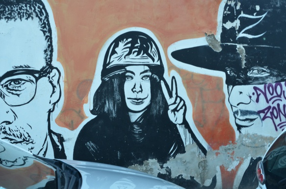 woman in hard hat giving peace symbol with hand, large portraits by sten and lex, Italian street arts, in a mural on two sides of the street, of famous people and common people,