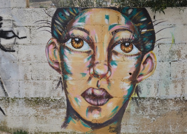 realistic painting of a woman's face in colur, short hair, light brown eyes, lips are slightly crooked, on a concrete wall, by Batool Edris