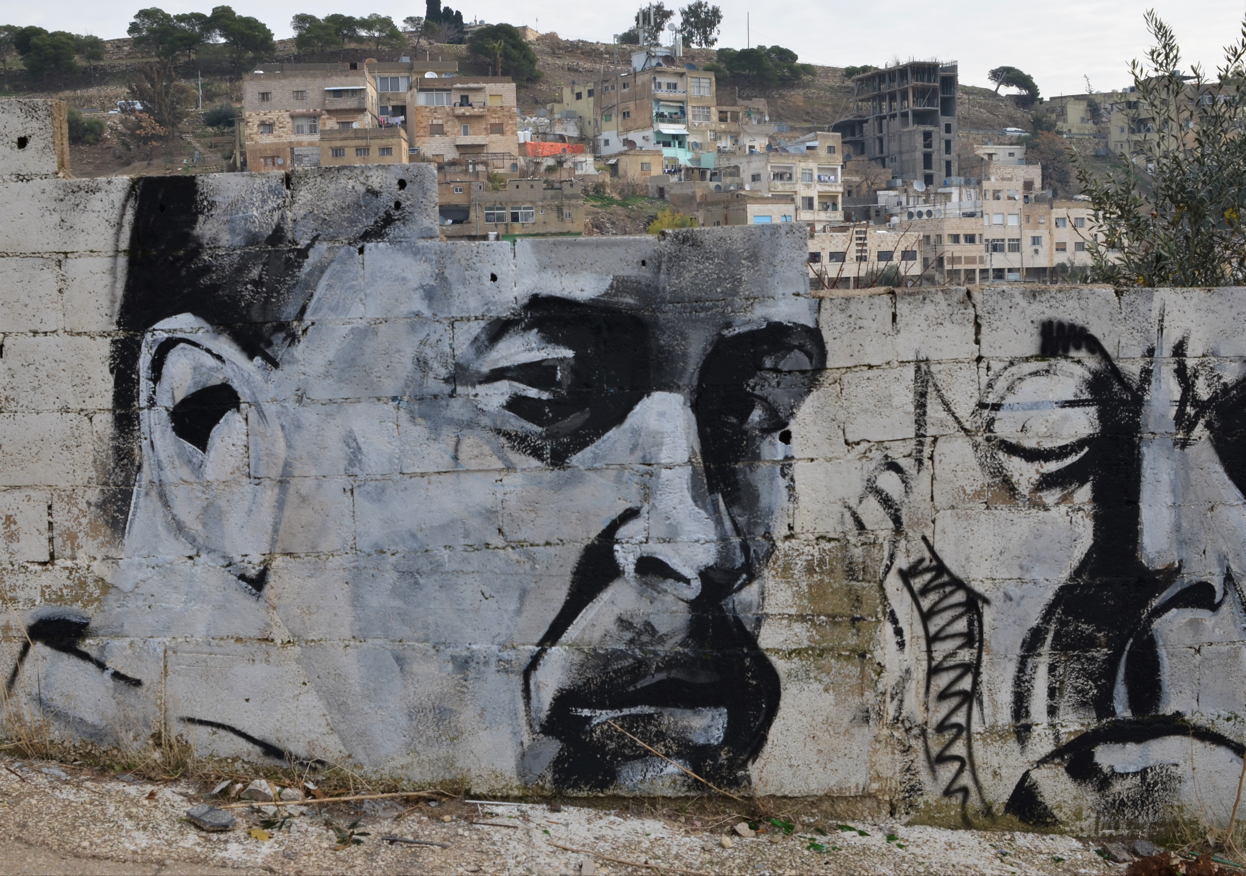 Black and white, grey tones, painting of a man's face in partial profile, on a wall. Can see the city beyond over the top of his forehead