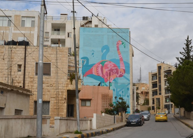 large mural of a pink flamingo seen from down the street