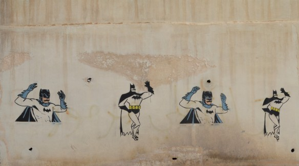 on a wall, 4 stencils of Batman, two have him dancing and two have him playing castonettes