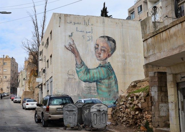 mural by Herakut of a child with a caterpillar on his or her finger, words around the child in both Arabic and English