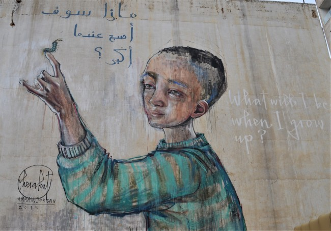 close up photo of mural by Herakut of a child with a caterpillar on his or her finger, words around the child in both Arabic and English showing more details of the child withshort dark hair and a green and grey striped long sleeved shirt