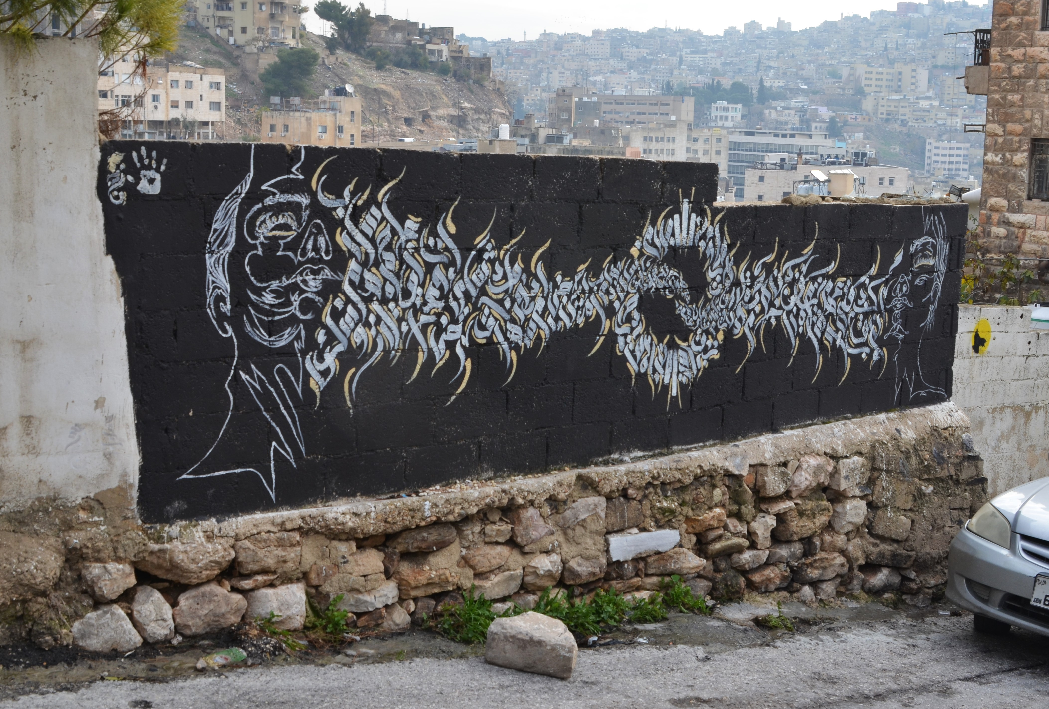 black and white mural of two faces, one at each end, with arabic letters between them