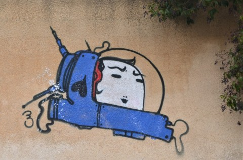 smallpainting on a concrete wall of a small blue spacecraft with a large white face inside it
