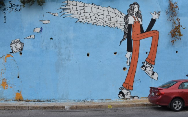 a very tall skinny woman with white wings and long dark hair in a mural, standing ith one leg raised bent at the knee. She's wearing orange overalls and white boot-like shoes. She has a small white folded paper boat in one hand