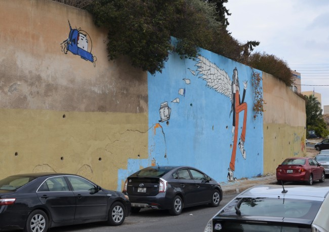 cars parked beside wall with blue mural of tall skinny woman with wings and small blue spaceship