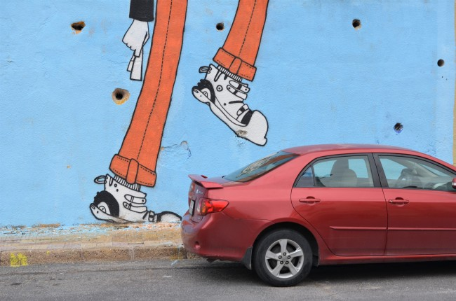 part of mural showing woman's legs, one leg raised looking like it's going to stomp on the red car that is parked beside the wall