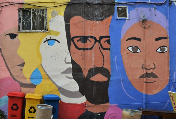 mural of large faces by the Orenda Tribe