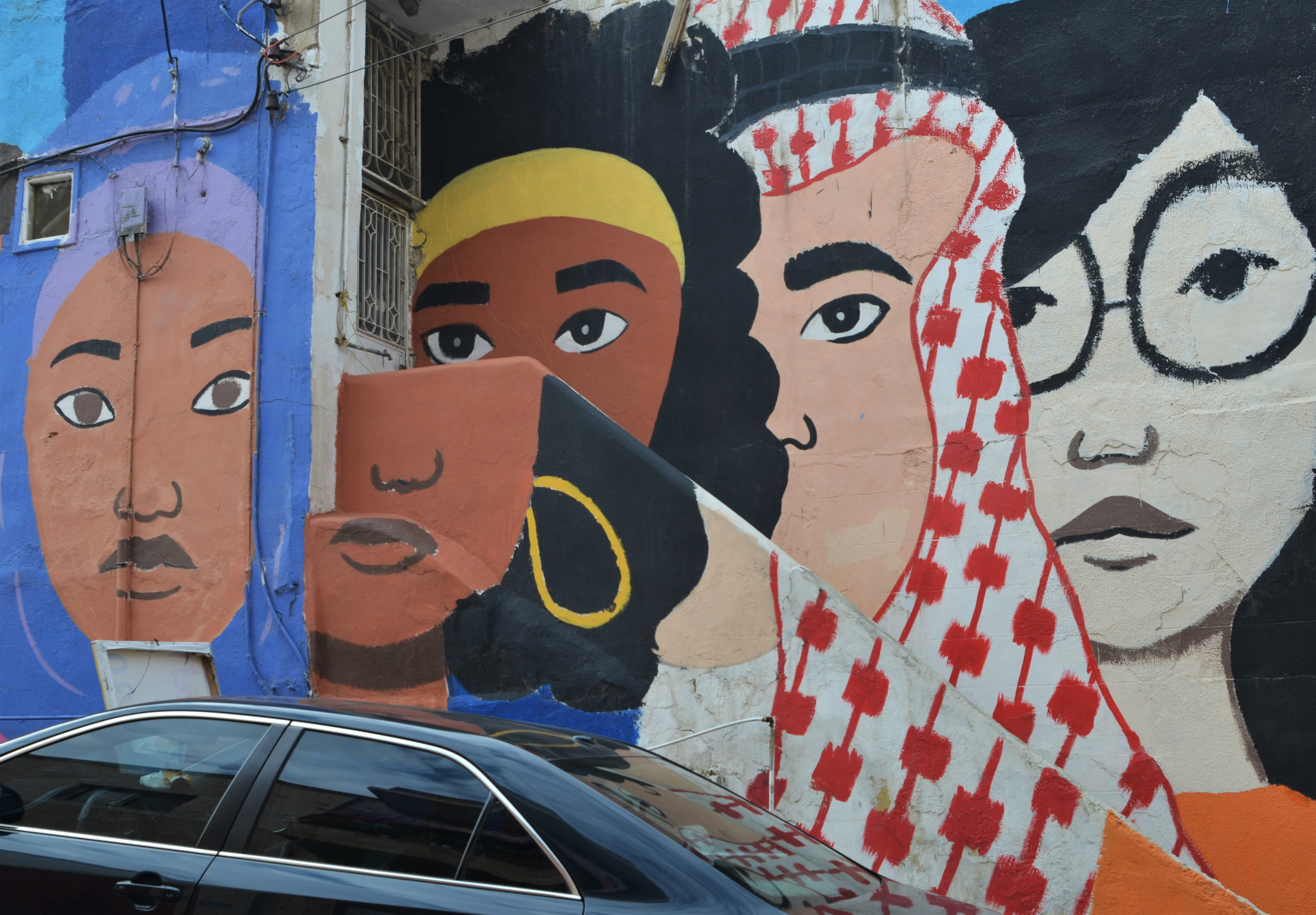 mural of large faces of different colours,
