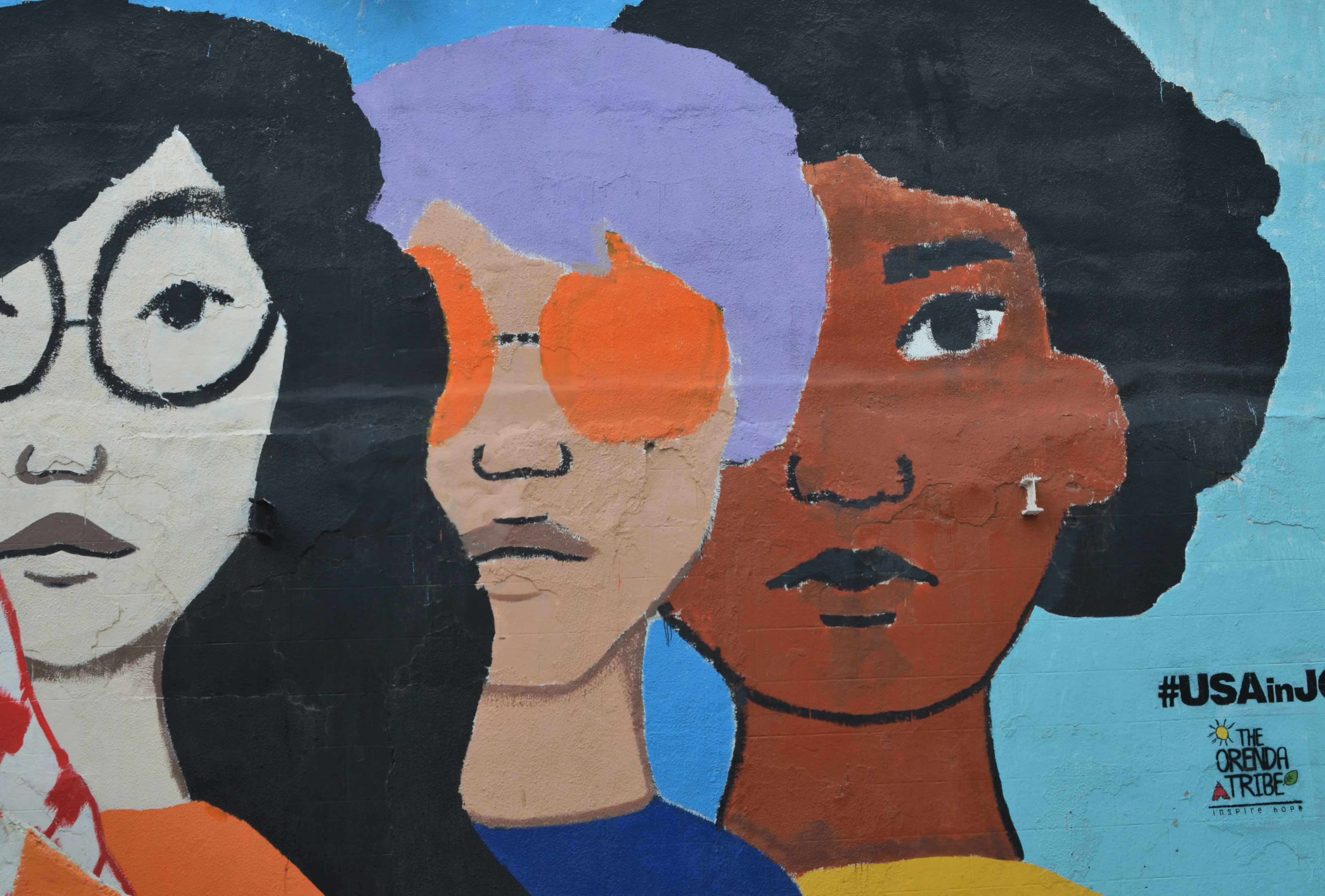 three large facecs in a mural, one with orange sunglasses and purple hair, one Asian looking with large black glasses