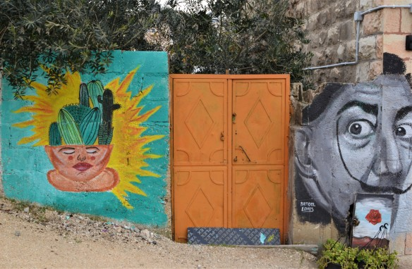an orange metal gate in between two murals, on the left is face with a cactus instead of hair, and on the other side is a back and white picture of Salvator Dali